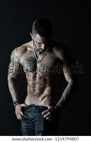 Fashion man with tattoo take off jeans. Man stripper show sexy torso. Sportsman with six pack and ab stripping. Athlete with biceps and triceps muscles. Desire and attraction, vintage filter. #1214794807