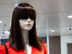 Fashion mannequin with long straight brown hair in department store boutique wearing  current women's fashions in red clothes.