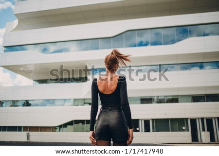 Fashion model at Zaha Hadid Dominion Tower exterior, Moscow, Russia