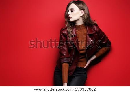 fashion model  beautiful young woman. leather jacket, studio shot, red background