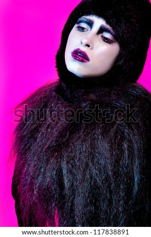 fashion model close-up portrait on pink color background in black clothes long dark hair