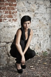 Fashion model crouching against brick wall