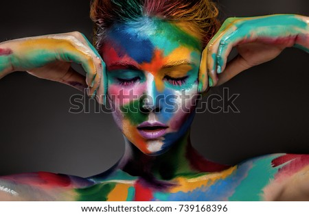 Stock Photo Fashion model girl portrait with colorful paint make up. Sexy woman bright color makeup. Art design. Grey background