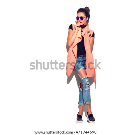 Stock Photo Fashion Model girl wearing sunglasses isolated over white background. Beauty stylish brunette woman posing in fashionable clothes in studio. Casual style, beauty accessories. High fashion urban style