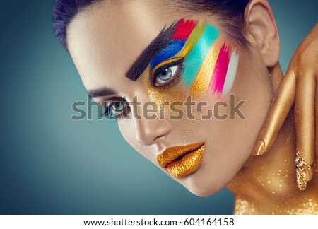 Fashion Model Girl with colored face painted. Beauty fashion art portrait of beautiful woman with colorful abstract makeup. Vivid paint make-up, bright colors. Vogue style lady face, Multicolor design