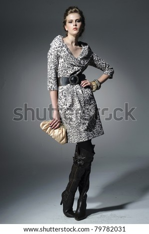 fashion model holding little purse posing in light background