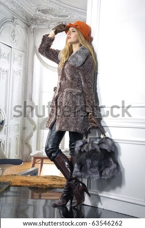 fashion model in autumn/winter clothes in hat with handbag posing in the studio