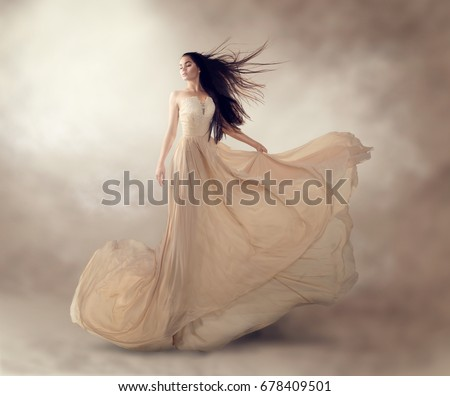 Fashion model in beautiful luxury beige flowing chiffon dress, Woman in long flying evening dress with a gown, Stunning fantasy model. Silk fabric waving on wind. Satin Cloth Flowing, Waves of a dress