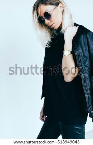 Fashion model in black clothing. Leather jacket and pants, blank t-shirt and sunglasses. Street urban minimalist style.