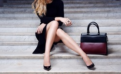 Fashion model in black dress with big leather red handbag in high heel shoes sitting on the white stair