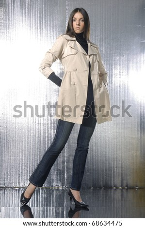 fashion model in coat clothes posing in light background