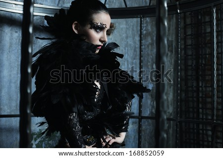 Stock Photo Fashion model in fantasy dress posing in steel cage.