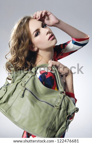 fashion model in modern clothes with green bag