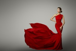 Fashion Model in Red Beauty Dress, Sexy Woman posing evening Gown, Flying Silk Tail over gray background