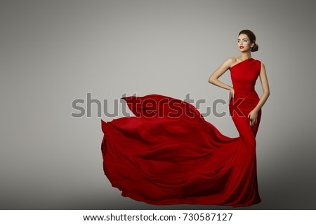 Fashion Model in Red Beauty Dress, Sexy Woman posing evening Gown, Flying Silk Tail over gray background #730587127