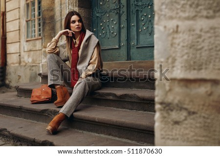 Fashion Model In Street. Beautiful Sexy Woman In Stylish Fashionable Fall Clothes: Shirt, Scarf, Pants, Sweater, Shoes Sitting On Stairs In Spring. Girl In High Fashion Autumn Clothing Posing Outdoors