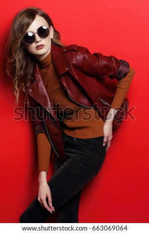 fashion model in sunglasses, beautiful young woman. leather jacket, studio shot, red background