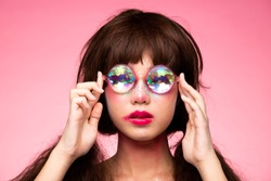 Fashion Model looks at camera for shooting new collection Sunglasses.  Beautiful Asian Woman set afro hair trend make up wear Kaleidoscope Glasses with colorful, studio lighting pink background