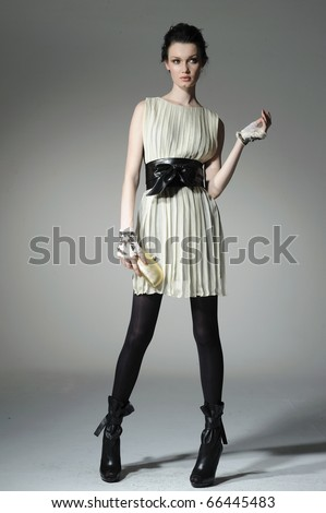 fashion model model holding little purse on gray background - stock photo