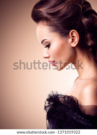 Fashion model. Model with a long curly hair. Creative hairstyle. Beautiful face of an young  woman in black dress posing at studio.