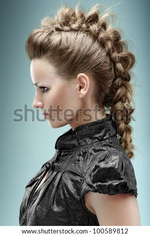 Fashion model posing  in the studio with hairstyle in a black short blouse. Hairdressing.