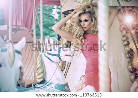 Fashion model posing on carousel in pretty summer dress