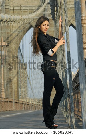 Fashion model posing sexy in short black dress on Brooklyn Bridge in New York