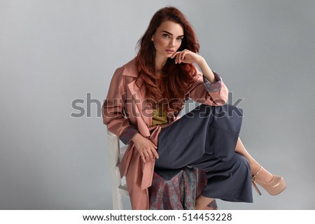 Fashion Model Style. Fashionable Woman In Stylish Clothes Posing On Grey Background In Studio. Beautiful Sexy Girl Wearing Pink Coat, Purple Trousers, Beige Shoes Sitting On Chair. High Resolution