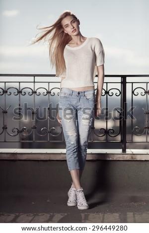 Fashion model. Summer look. Jeans, sneakers, sweater.