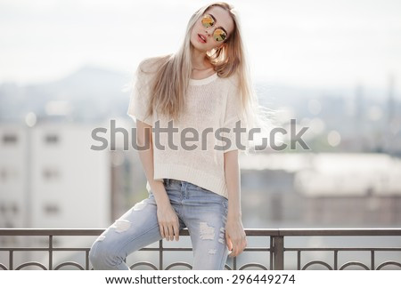Fashion model. Summer look. Jeans, sweater, sunglasses.
