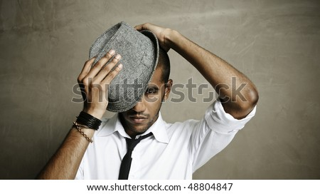 Fashion model tries his best to put his hat on correctly