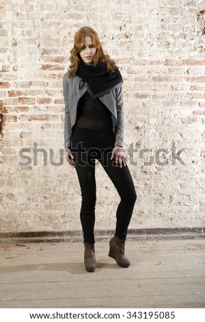 Fashion model wearing leather pants and jacket posing in the old building wall #343195085
