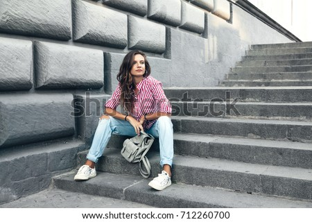 Fashion model wearing ripped boyfriend jeans, red striped shirt, sneakers and backpack posing in the city street. Fashion urban outfit. Casual everyday clothing style.