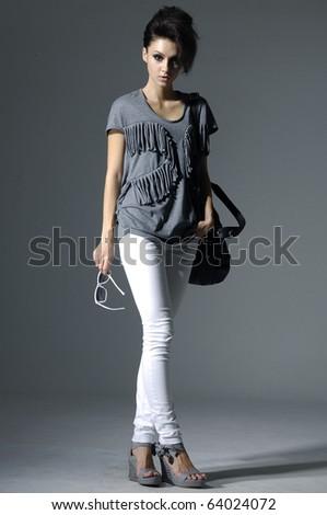 fashion model wearing sunglasses with handbag posing in light background