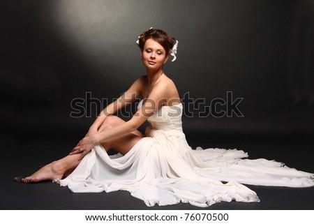 Fashion model wearing wedding dress at black studio background