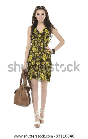 Fashion model wears elegant clothes holding handbag walking
