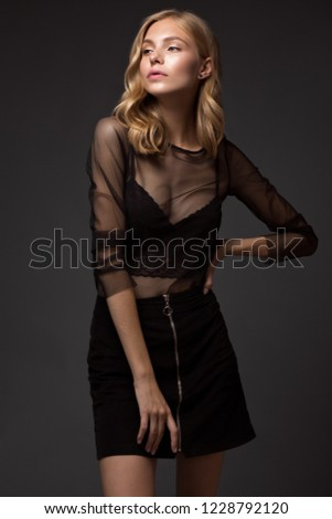 fashion model with long hair, beautiful eyes, perfect skin is posing in studio for glamour test photo shoot showing different poses. Picture taken in the studio on a gray background.