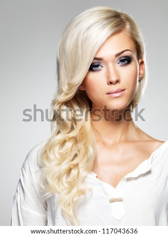 Fashion model with long white hair  and bright make-up. Portrait of glamour woman posing at studio