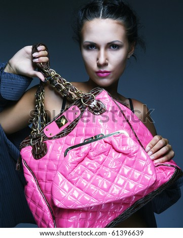 Fashion model with pink bag. posing in the studio