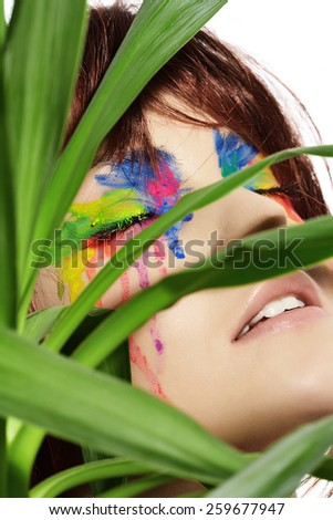 Fashion model with short dark fluffy hair and colorful make-up posing with a green plant.
