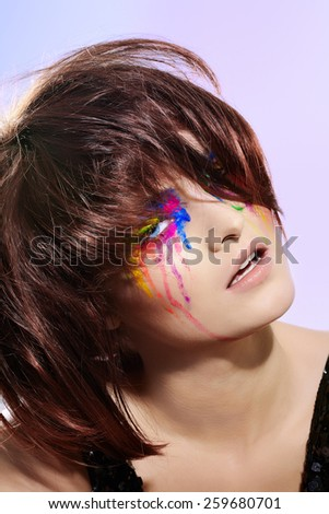 Fashion model with short dark fluffy hair and colorful make-up with paint effect.