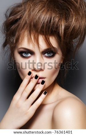 Fashion model with tousled hair, make-up, manicure. Portrait of young fashion woman with punk rock hairstyle, dark make-up, black nail polish