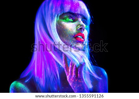 Fashion model woman dancing in neon light, disco night club. Beautiful dancer model girl colorful bright fluorescent make-up, painted skin, Body Art design of disco. Ultraviolet, UV, colorful make up