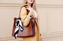 Fashion model woman in autumn outfit with big brown bag scarf. Trendy beige coat