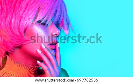 Fashion model woman in colorful bright lights, portrait of beautiful party girl with trendy make-up, manicure and haircut. Multicolored Art design, colorful make up. Over colourful vivid background. #699782536