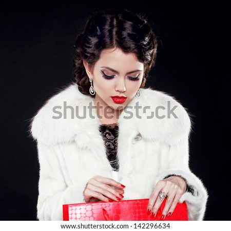 Fashion model woman in fur coat open shopping bag. Isolated on black background. Retro girl.