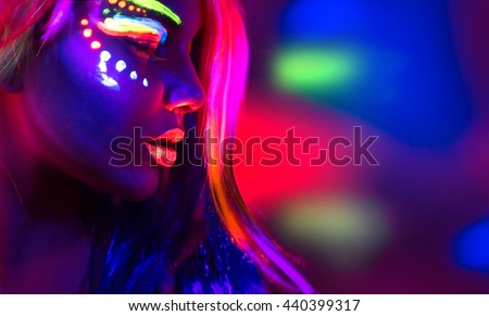 Fashion model woman in neon light, portrait of beautiful model girl with fluorescent make-up, Body Art design of female disco dancer posing in UV, painted face, colorful make up, over black background #440399317
