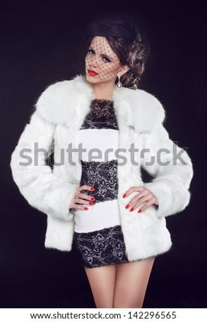 Fashion model woman wearing in luxury fur coat and elegant dress. Isolated on black background. Retro girl.