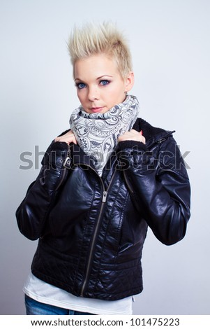 fashion model woman wearing scarf and black leather jacket on gray background - studio shot