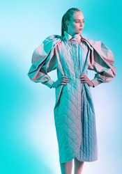 Fashion models girl poses in stylish clothes from the spring-summer collection. Full length studio portrait in aquamarine light. Haute couture clothing.